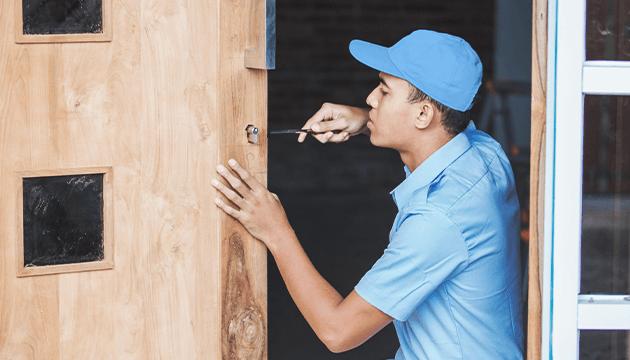 Locksmith installing a mortice lock on a wooden door