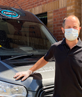 Locksmith wearing mask and glovs in front of NGCL van