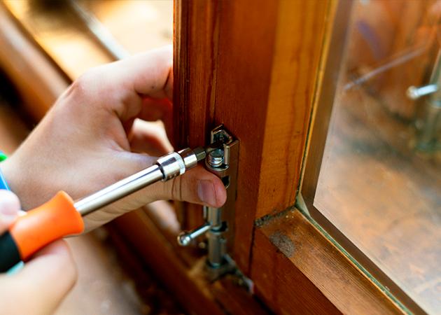 Locksmith Installing Window Locks on a wooden window