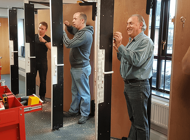 Men training to be locksmiths and practising on doors