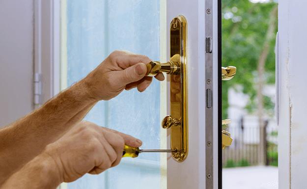 Locksmith changing lock on gold handle on a UPVC door