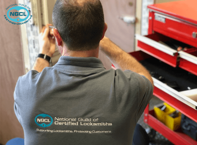 NGCL locksmith working on a wooden door